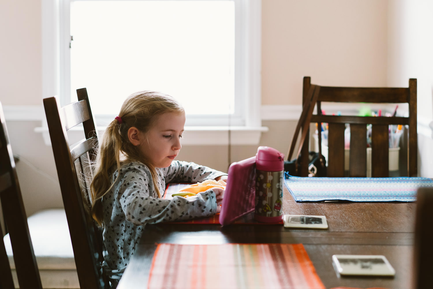 A little girl does her homework at the kitchen table.