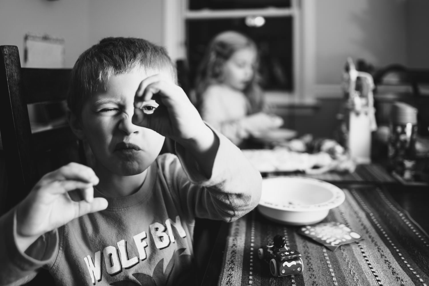 A little boy looks through a telescope he has made with his hand.