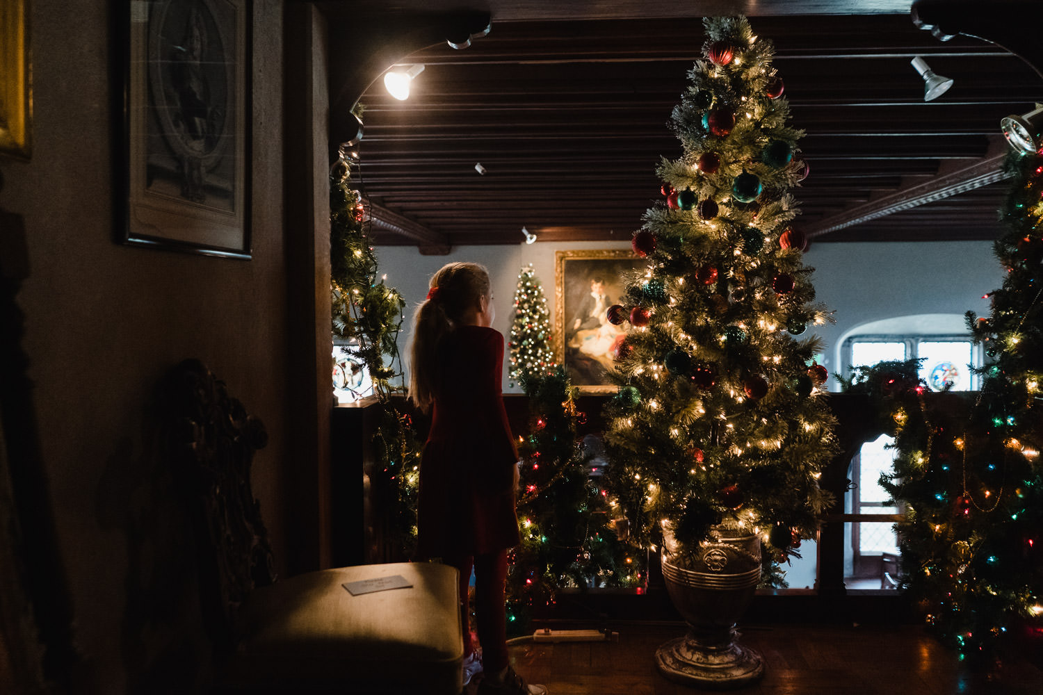 A little girl stands next to a Christmas tree at Coe House.