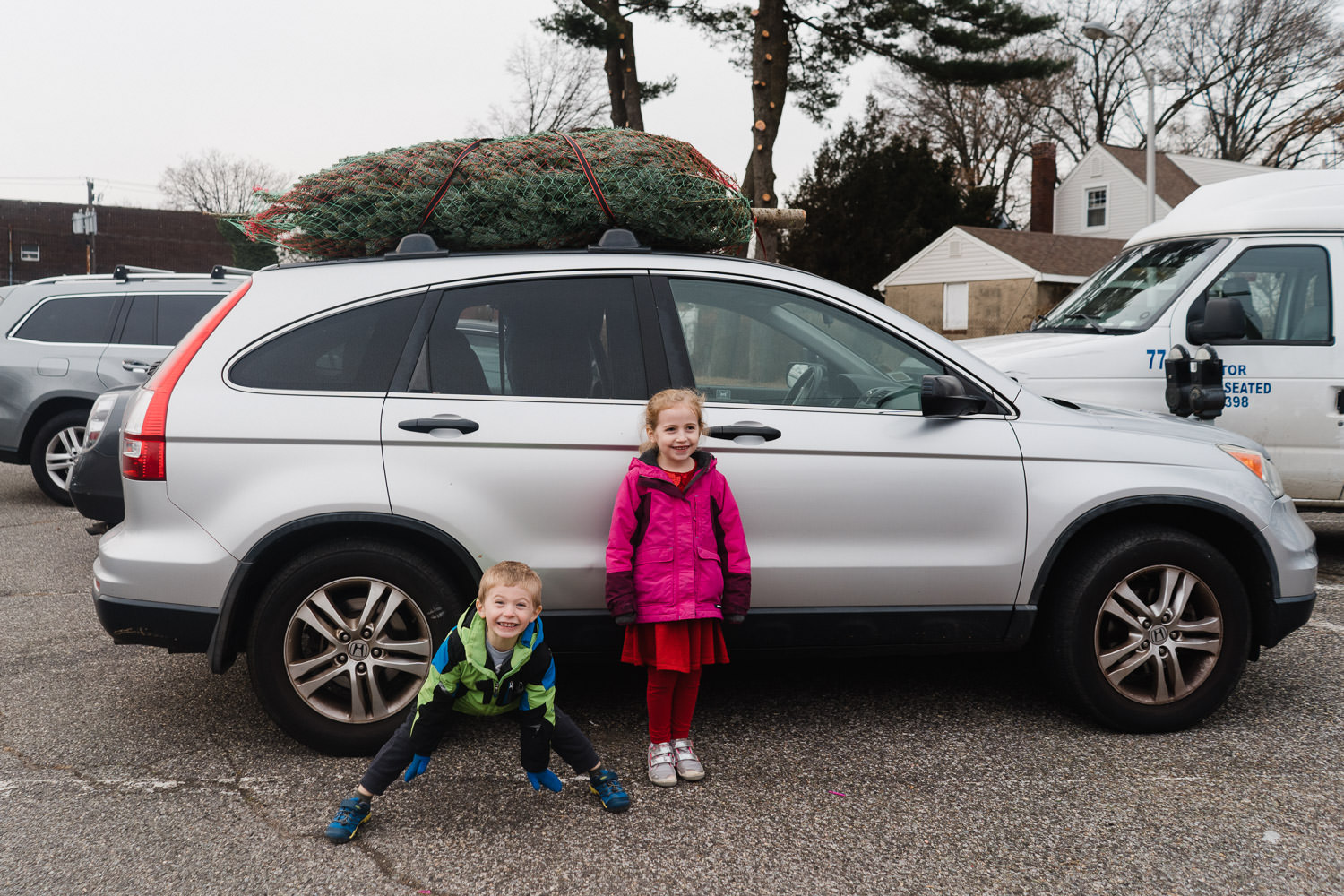 Two children stand in front of a car with a freshly cut Christmas tree on top.