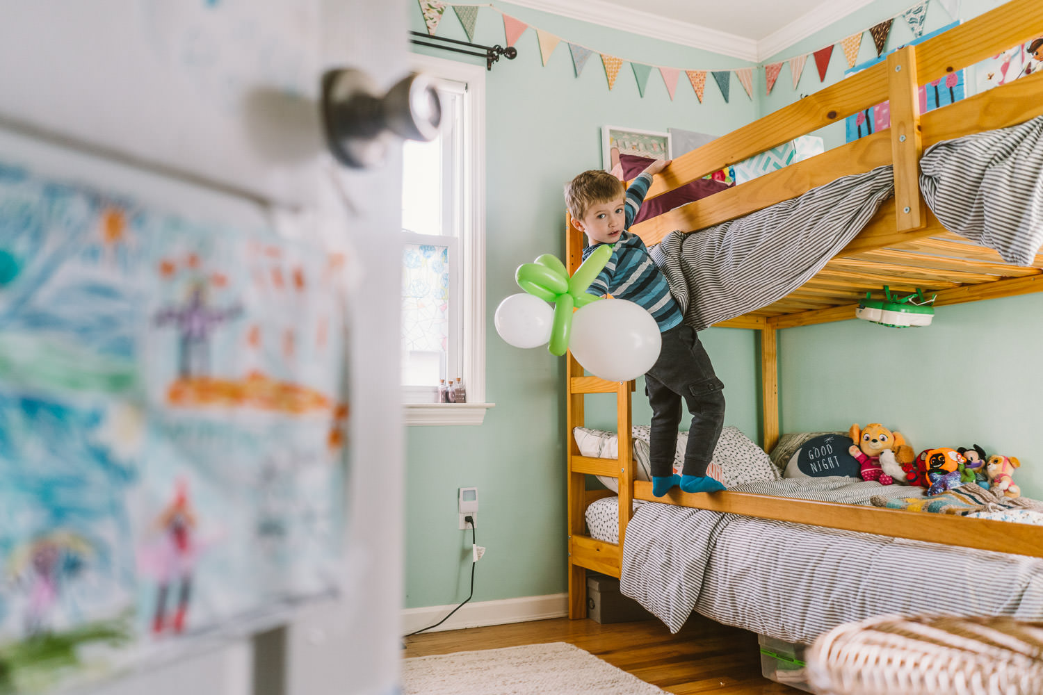 A little boy throws a balloon off a bunkbed.