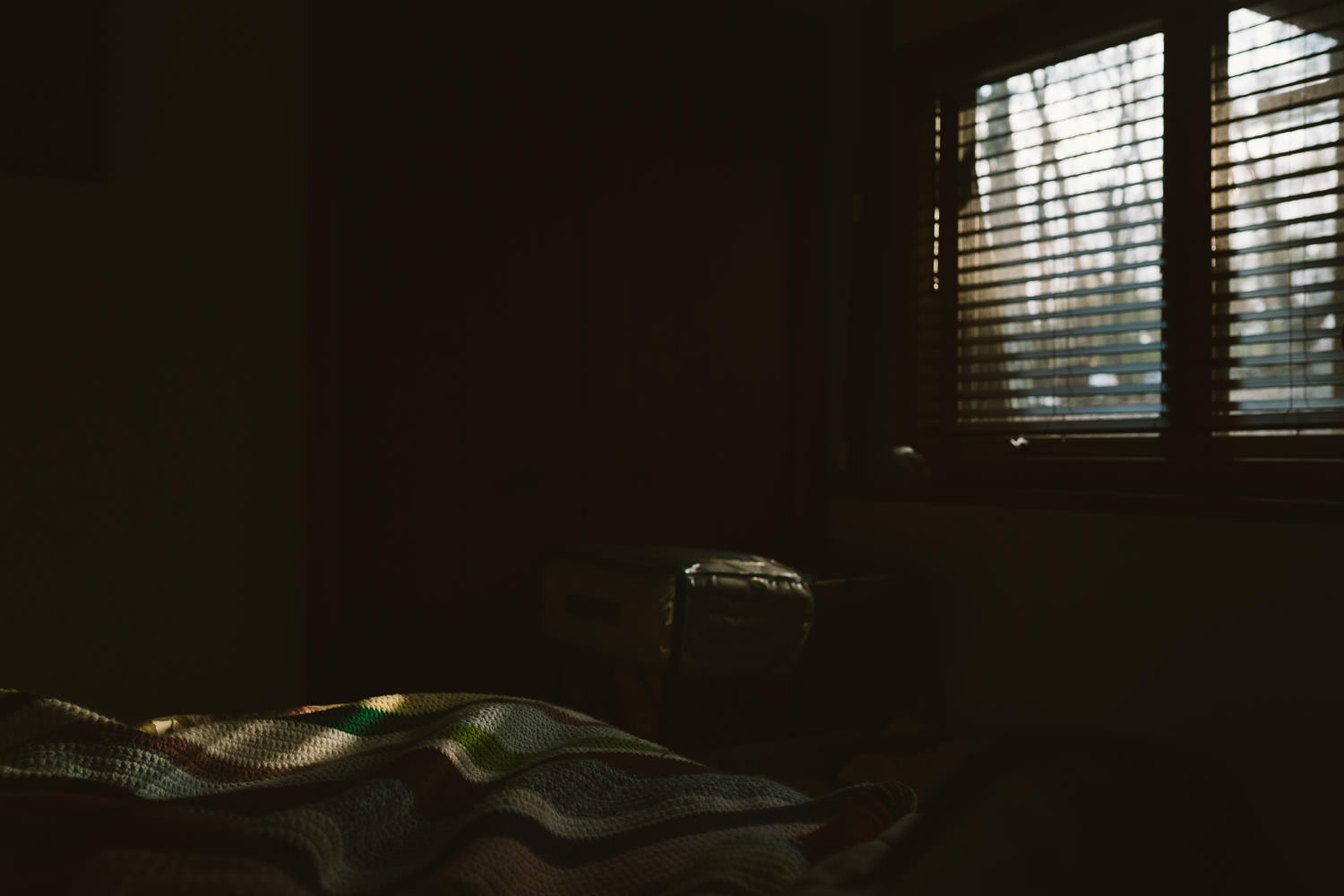 Sunlight filtering through shades in a bedroom.
