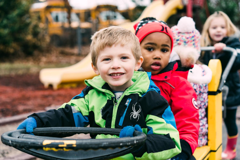 Children ride a wagon at preschool.