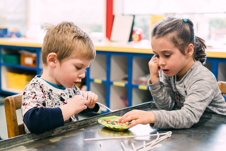 Two children thread beads.