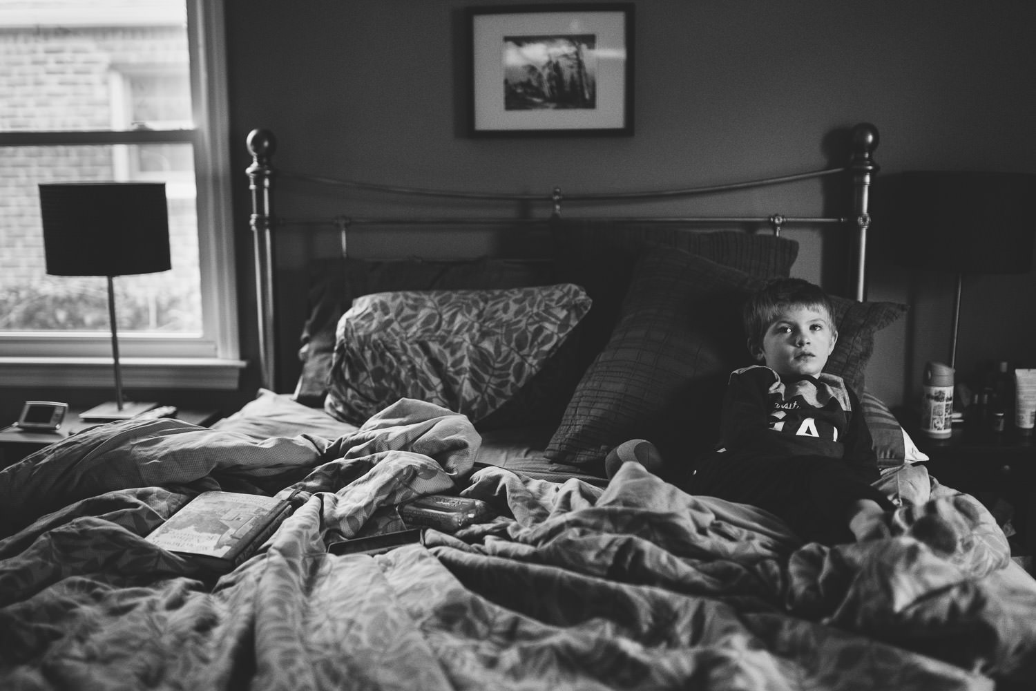 A little boy watches TV from his parents' bed.