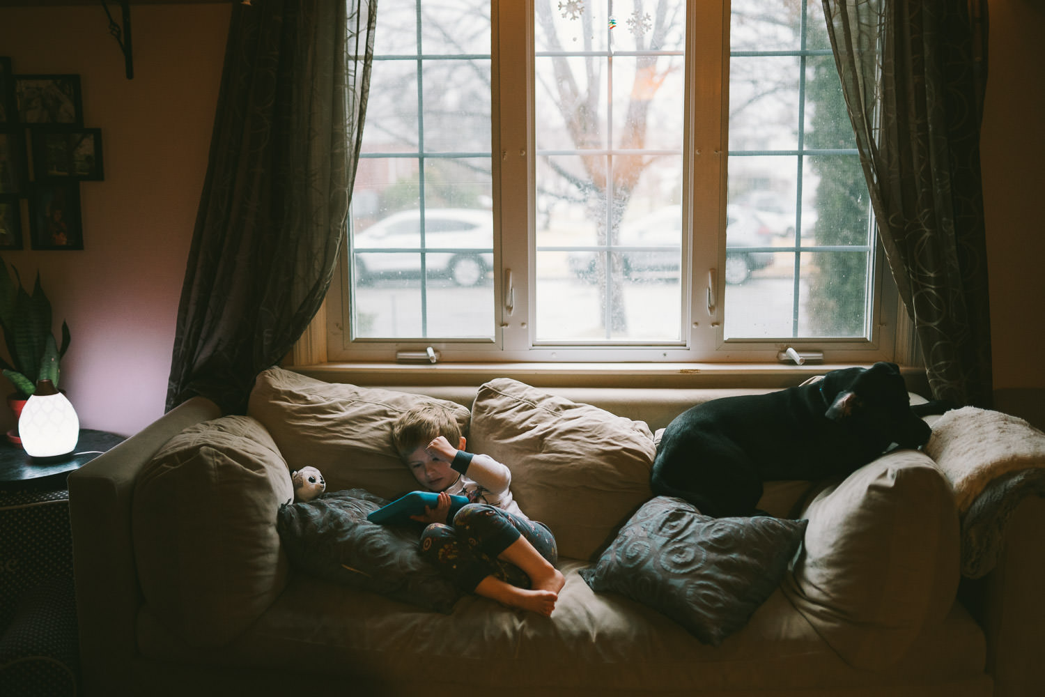 A boy and a puppy curled up on a couch.