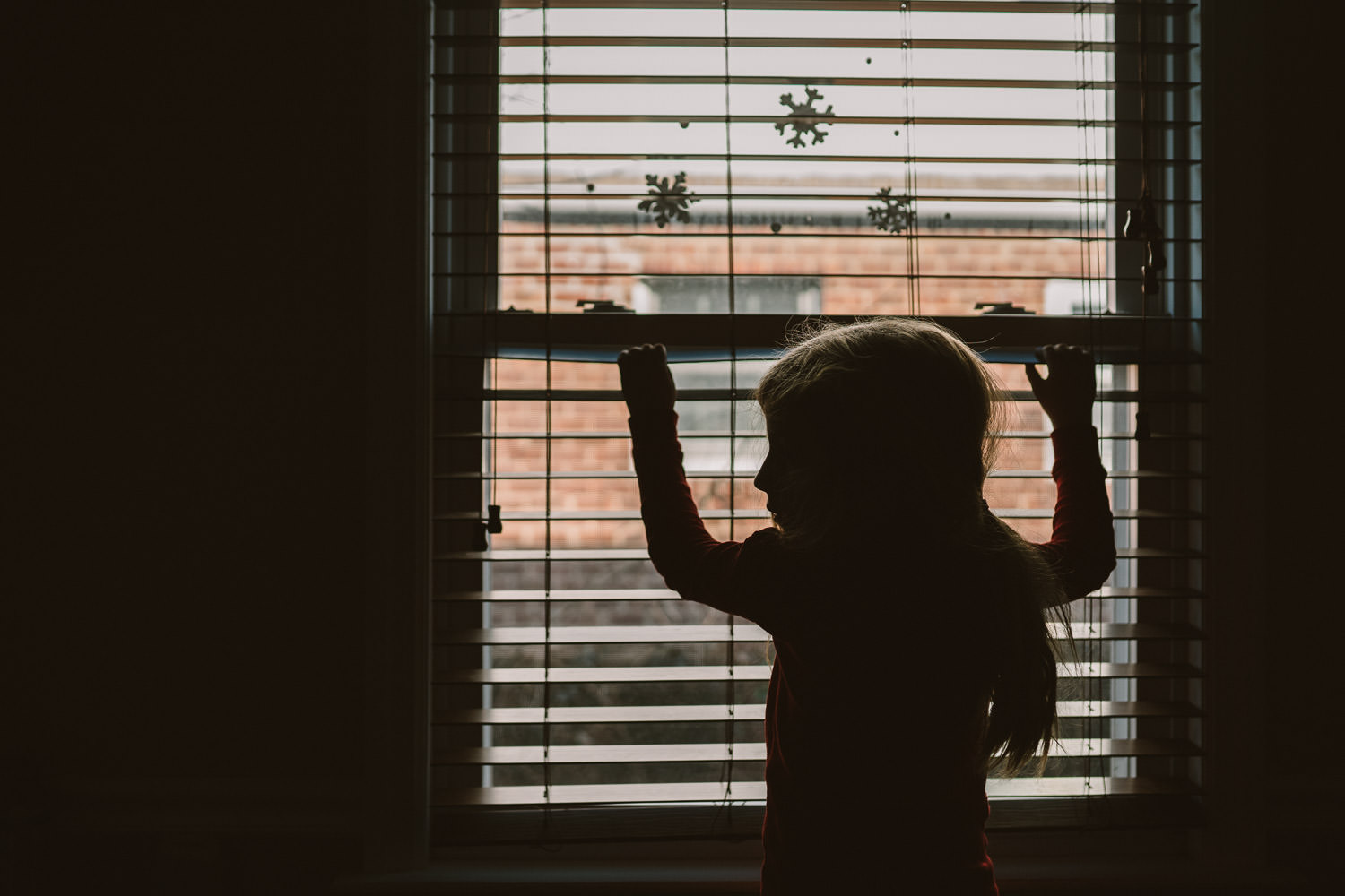 A silhouette of a little girl standing in front of a window with blinds.
