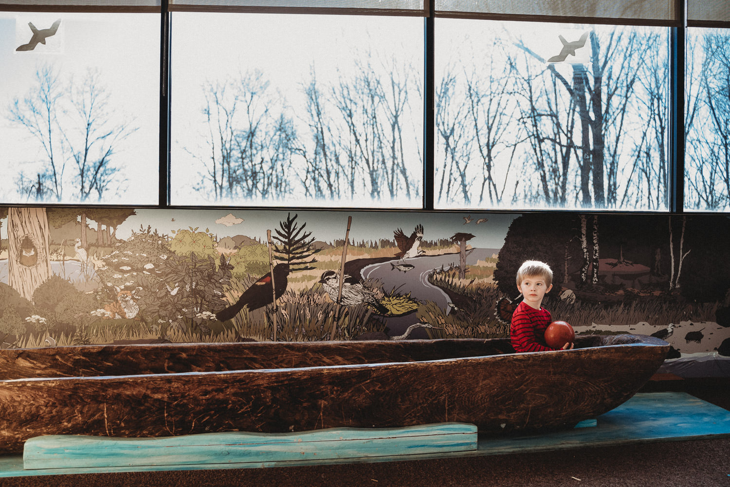 A little boy plays in a canoe at Garvies Point Museum.