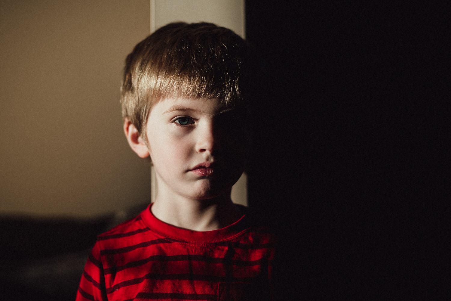 A portrait of a little boy in light and shadow.