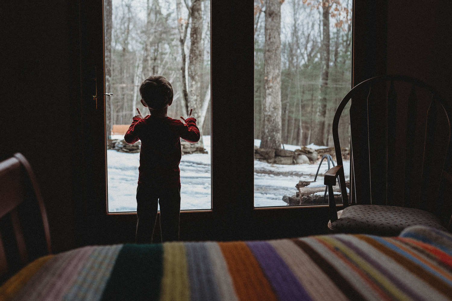 A little boy looks out a sliding door to a snowy scene.