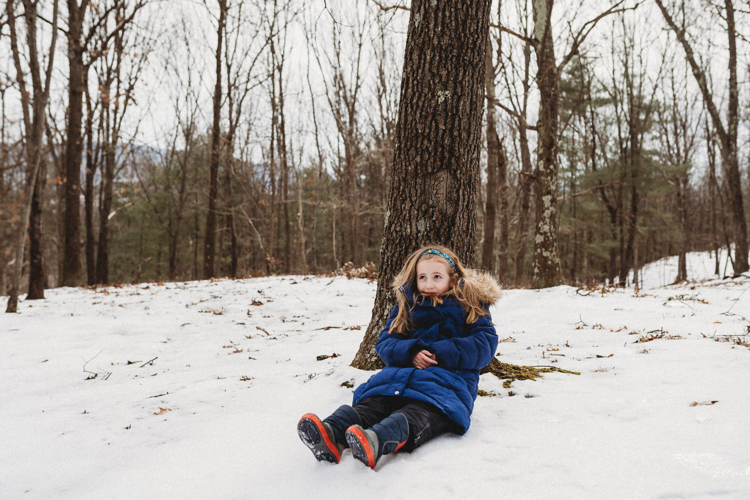 A little girl sits in the snow under a tree.