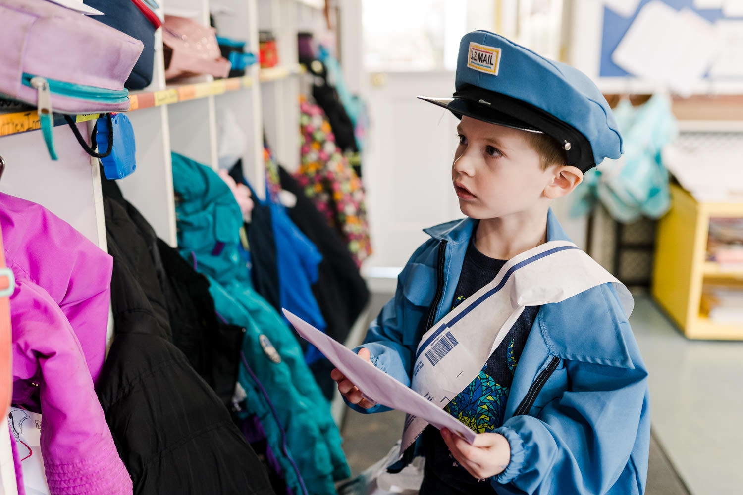 A little boy dressed as a mailman delivers envelopes to his friends' cubbies.