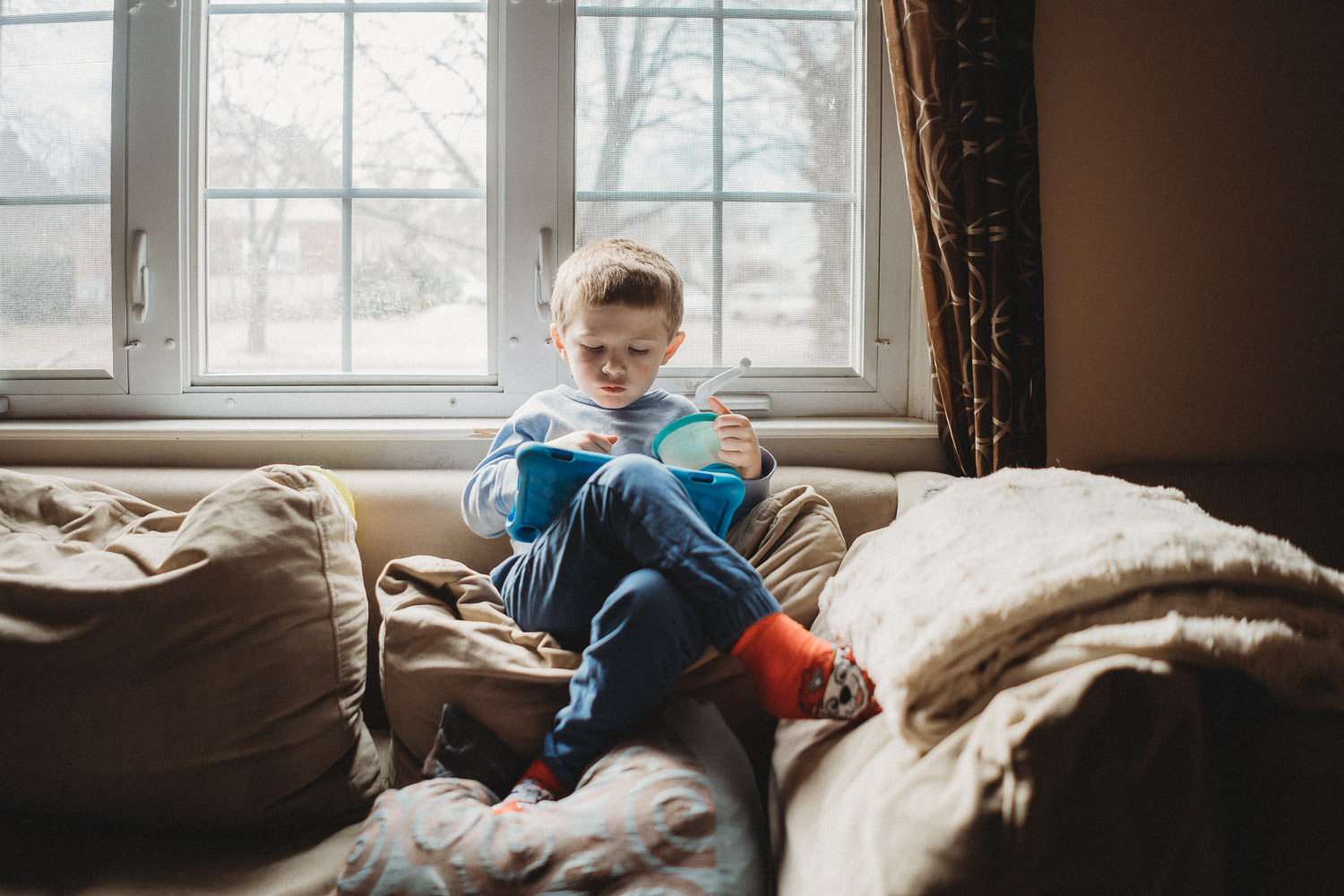 A little boy plays with his tablet on the couch.