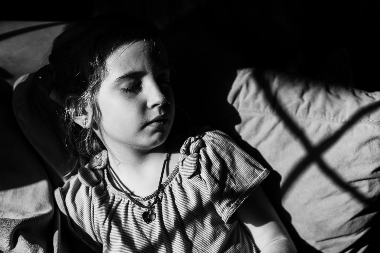 A little girl naps in the sun on a sofa.