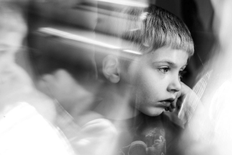 A little boy gazes dreamily out a window.