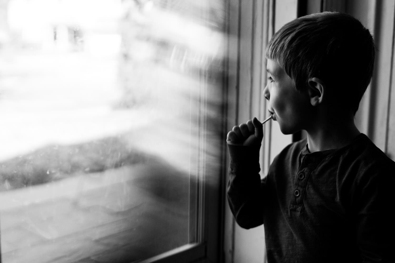 A little boy sucks on a lollipop at his front door.