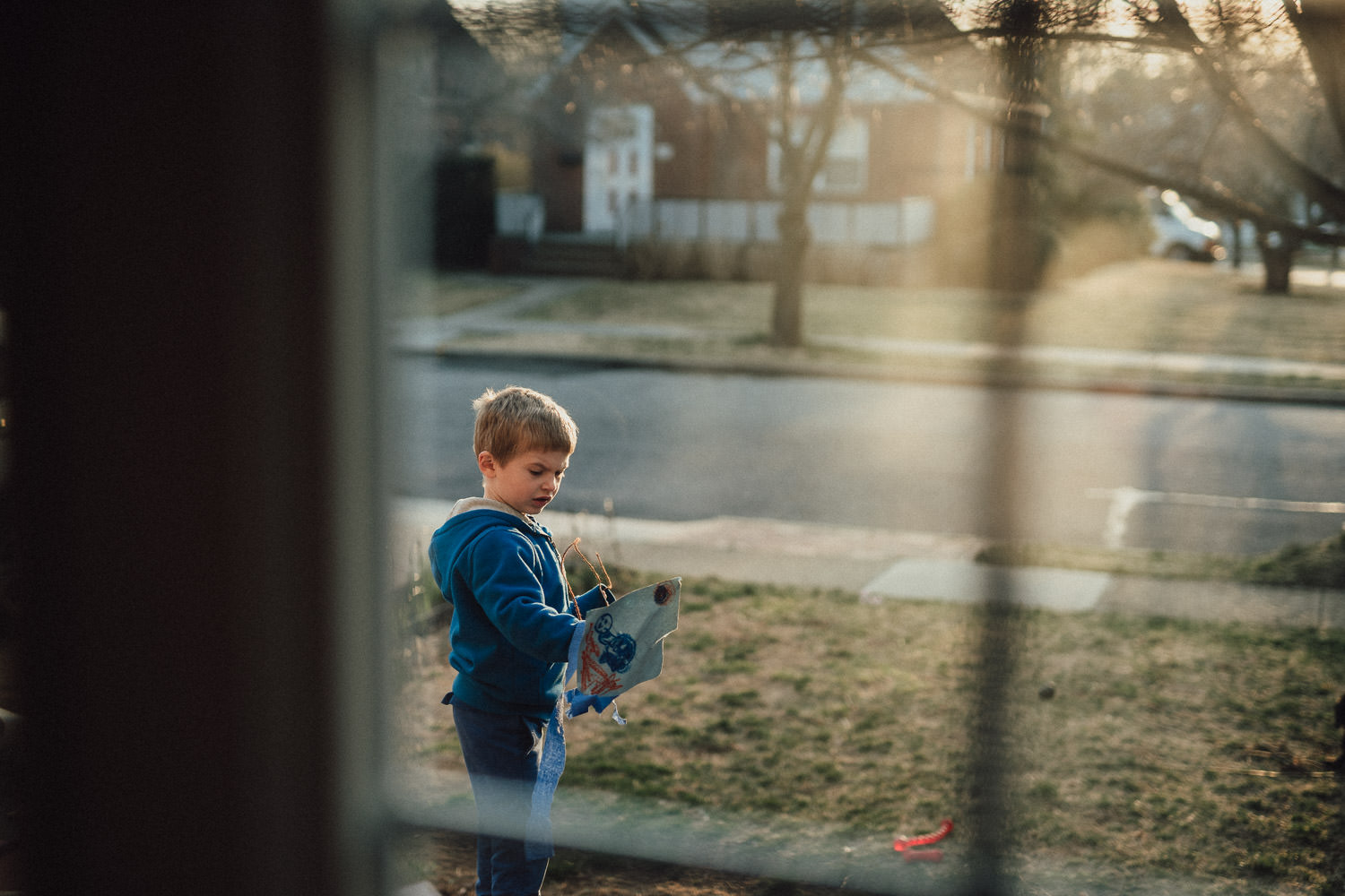 Looking through a window at a little boy outside.