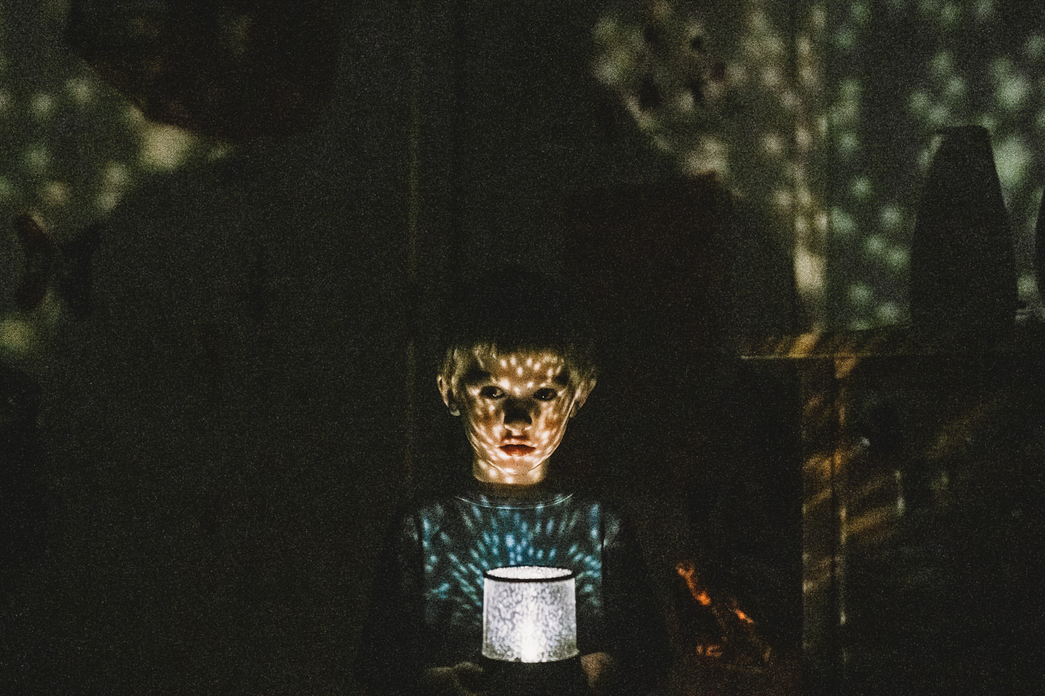 A little boy holds a nightlight in front of his face in a dark room.
