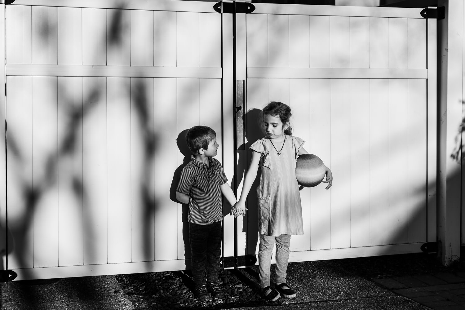 Two children hold hands in their driveway.