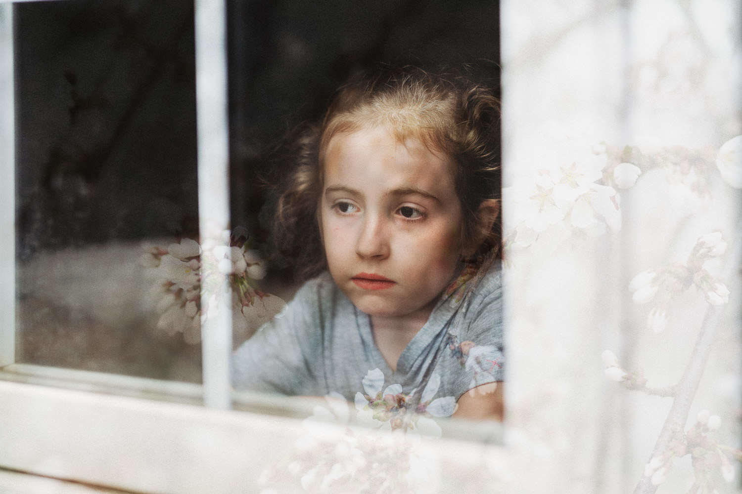 A little girl looks out a window with reflection of flowers on her face.