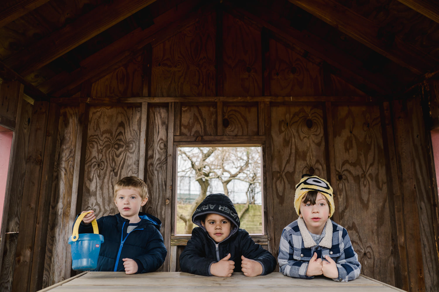 Three boys play in a clubhouse.