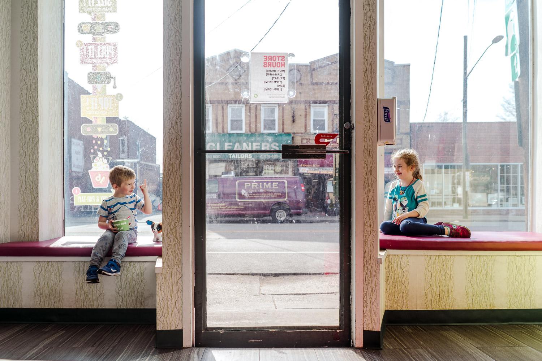 Two children sit in window seats at a yogurt shop.