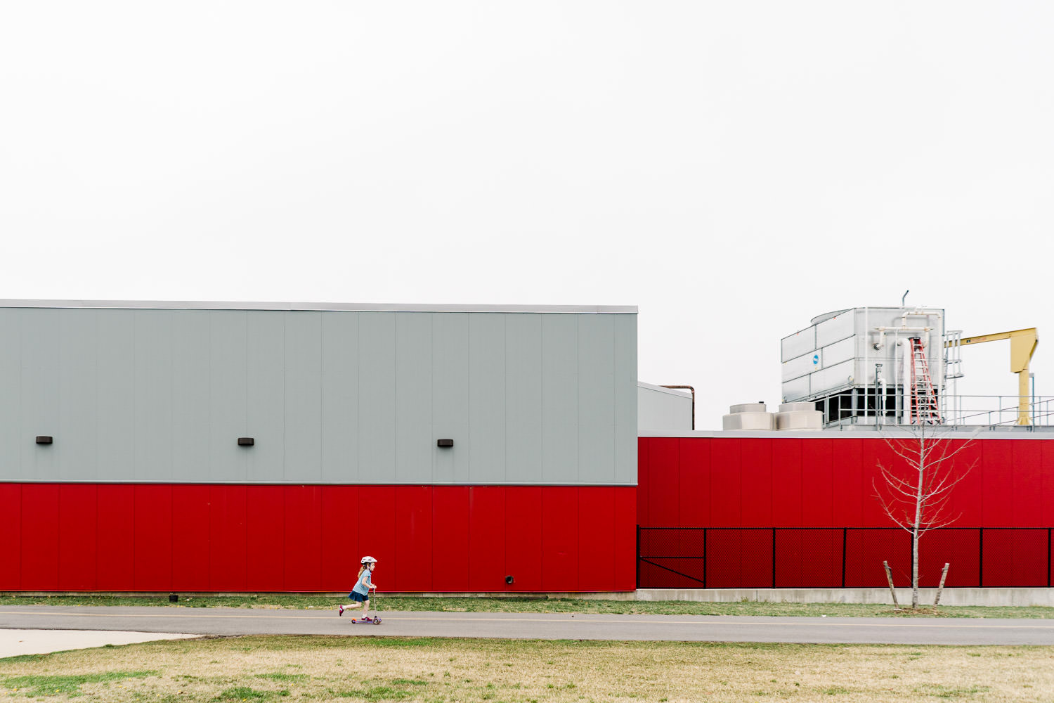 A child rides a scooter past a red building.