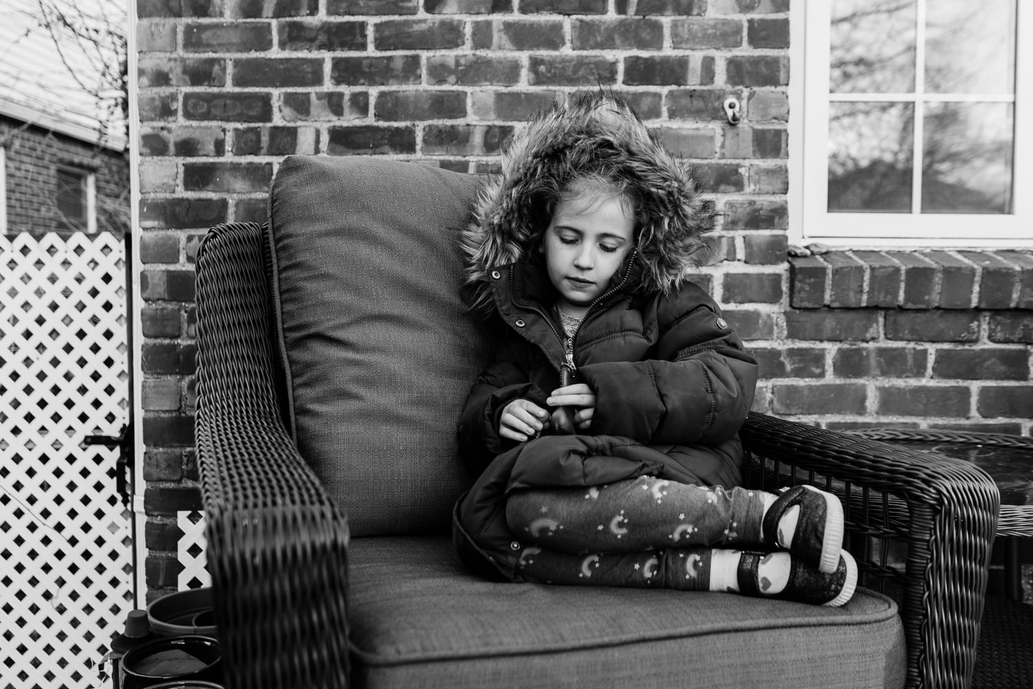 A little girl wearing a parka sits outside on a porch.