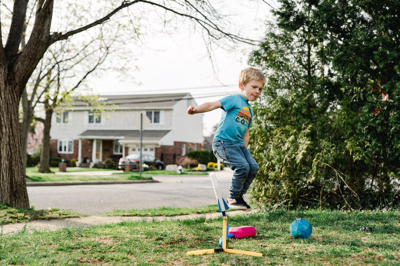A little boy jumps on a stomp rocket.