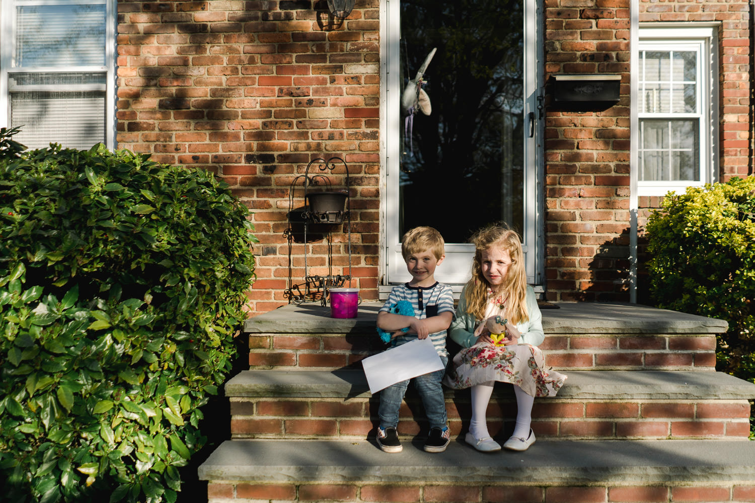 Two children sit on a sunny stoop.