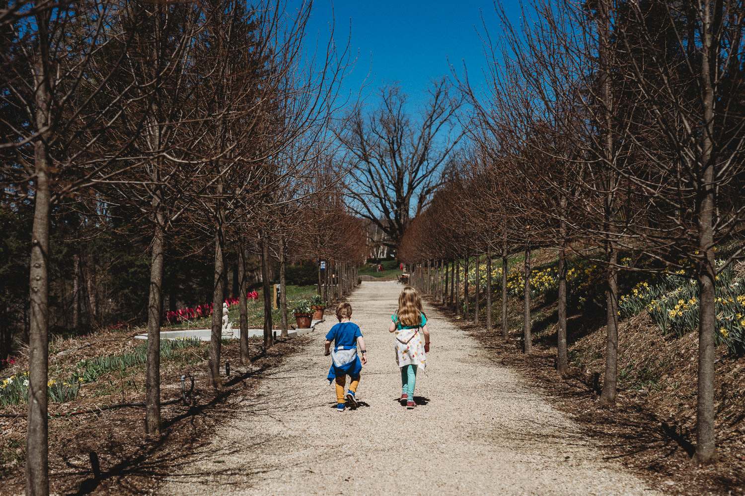 Two children walk down a path together.
