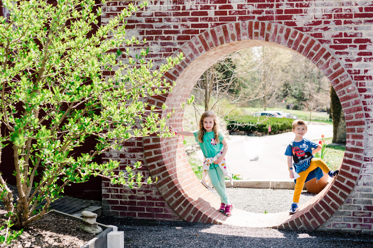 Two children stand in a circular entryway through a brick wall.