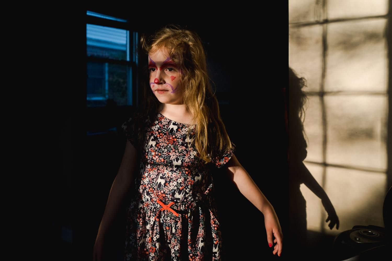 A little girl stands in golden light in her living room.