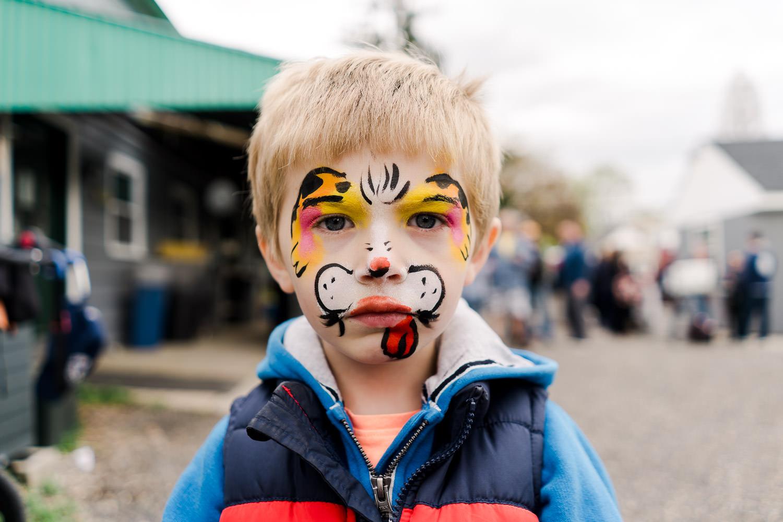 A little boy with doggie facepaint.
