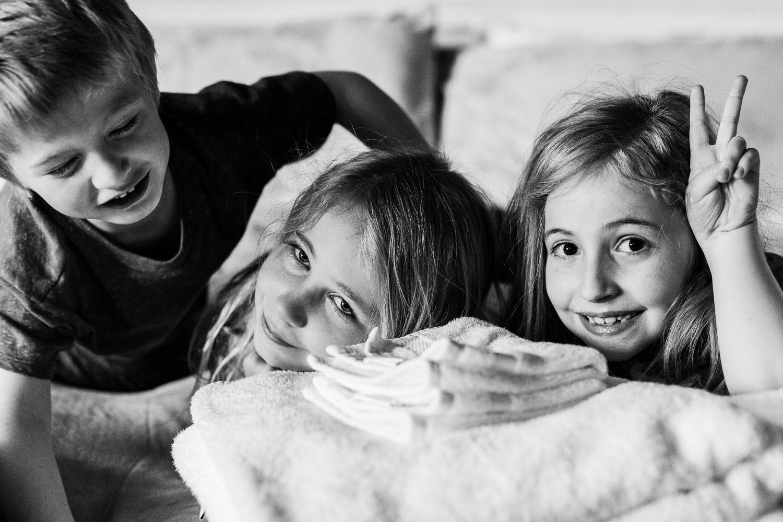Three children smile for the camera.