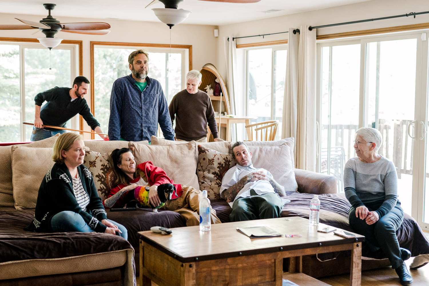 A family gathers in a living room.