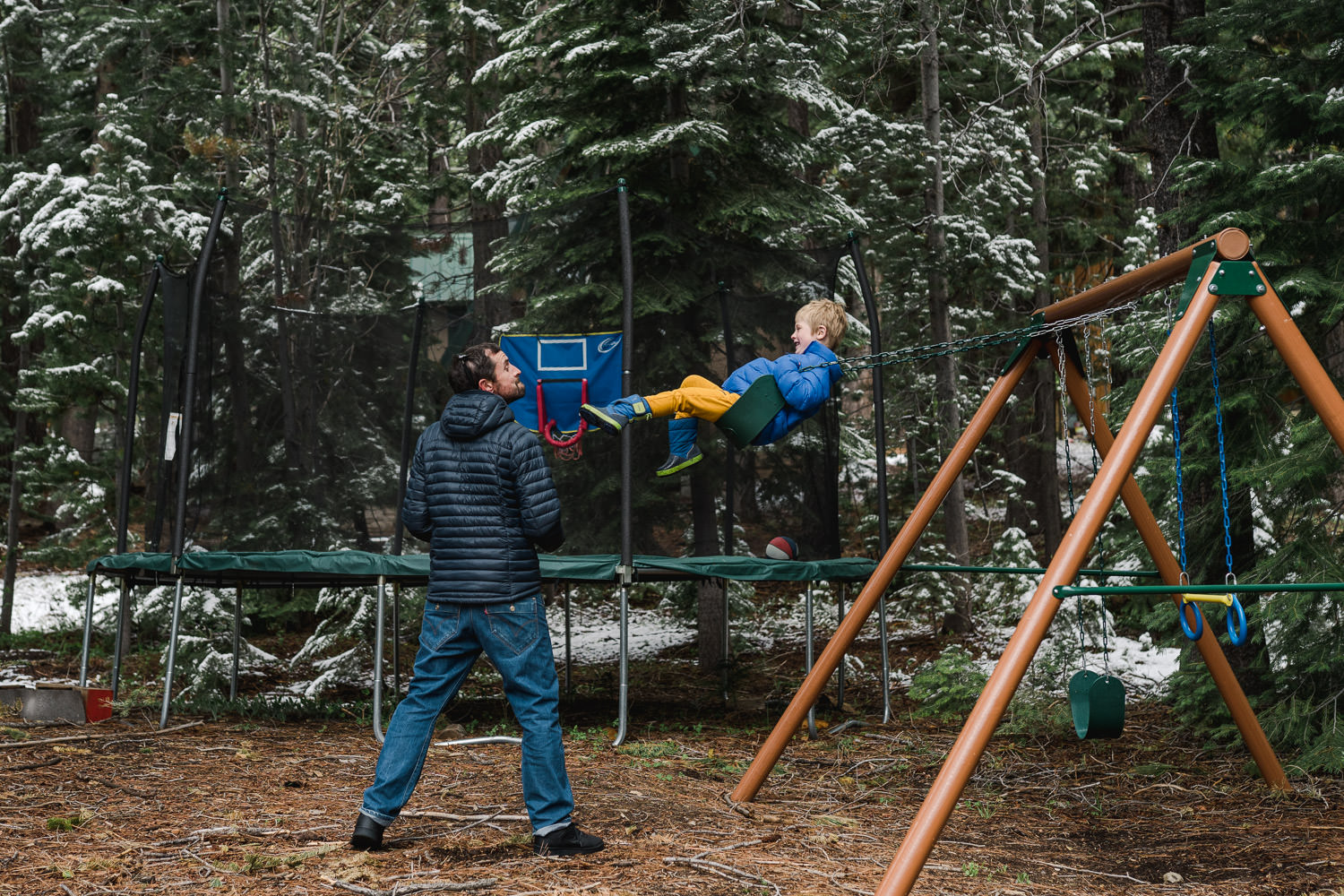 A little boy swings on a swing next to his uncle.