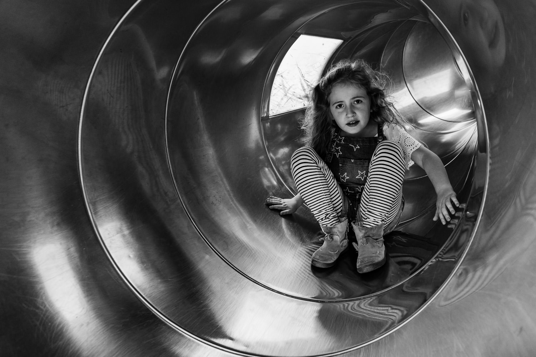 A little girl slides down a tunnel slide.