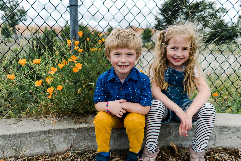Two children sit next to California poppies.