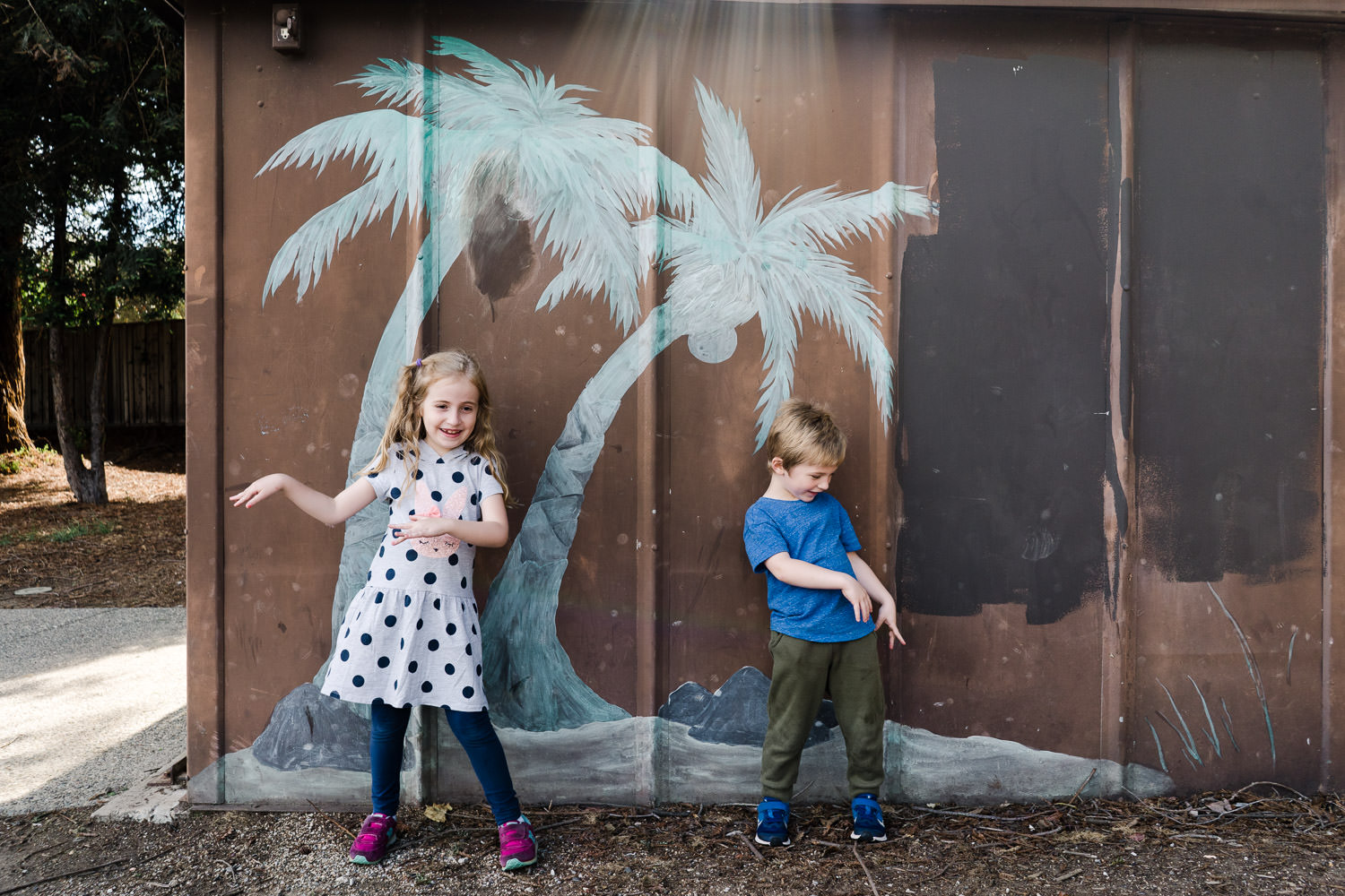 Two children dance in front of a mural of palm trees.