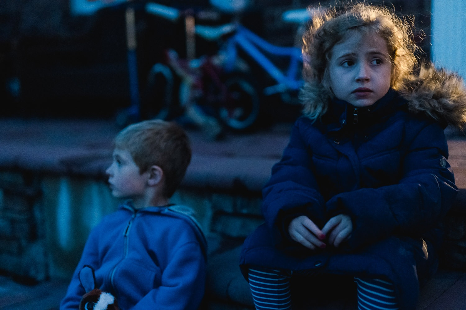 Two children sit on their porch at dusk.