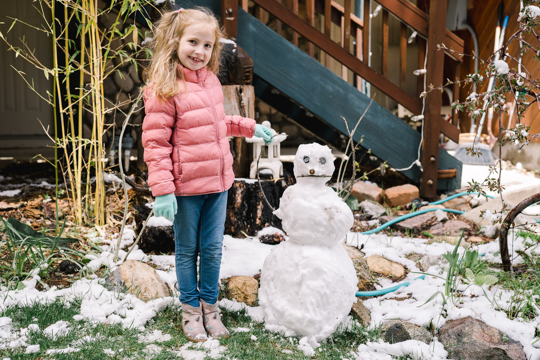 A little girl stands next to her snowman.