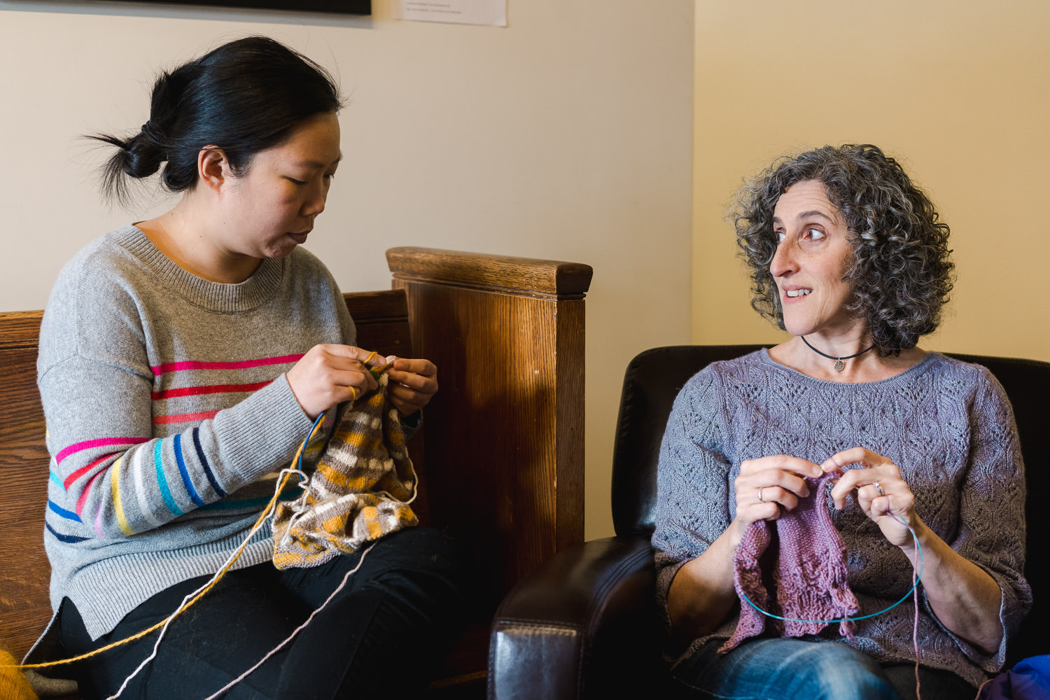 Two friends drink coffee together and knit.