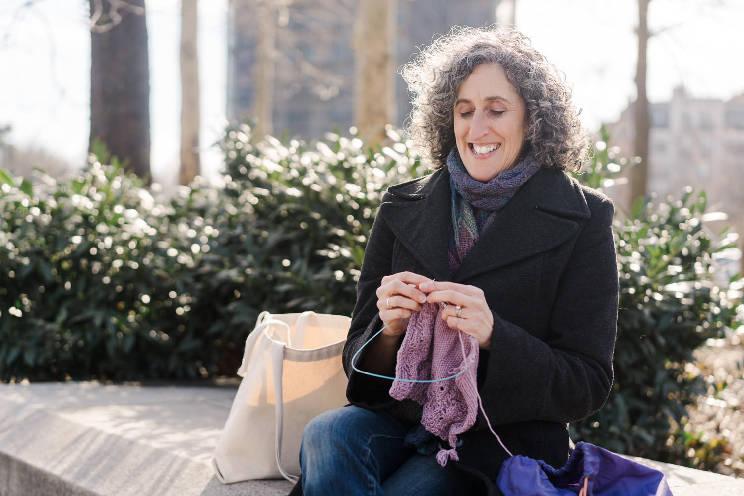 A woman sits in the park and knits.