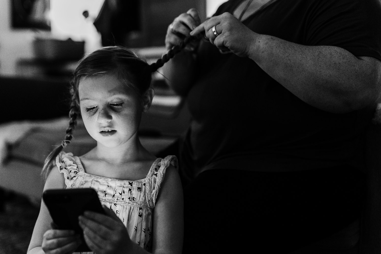 A little girl looks at a phone screen while getting her hair braided.
