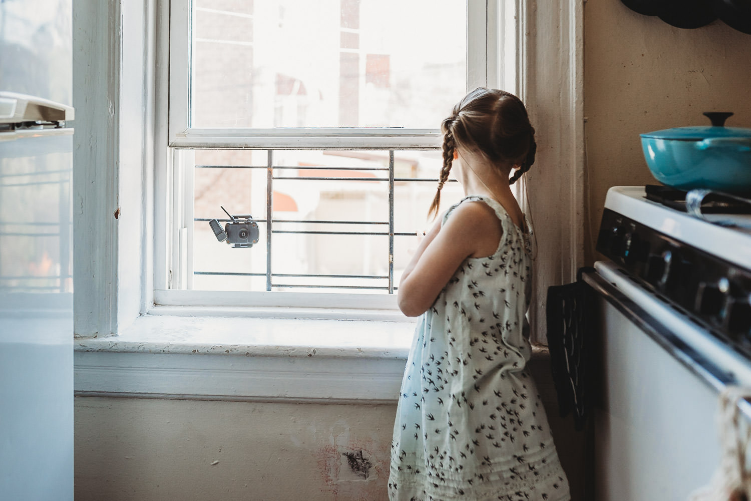 A little girl looks out a kitchen window.