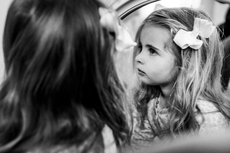 A little girl looks in a mirror.