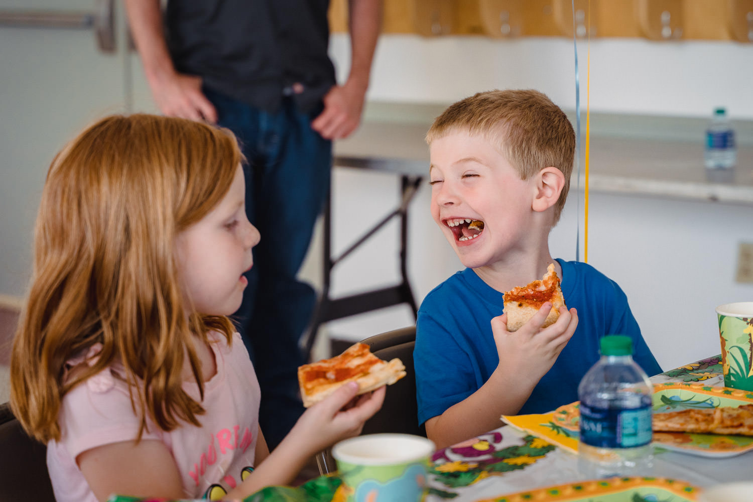 A boy and a girl laugh while eating pizza.
