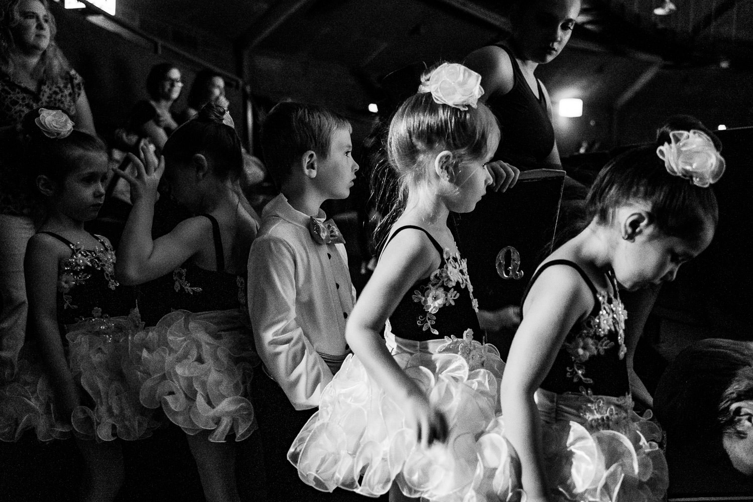 Children line up waiting to go onstage at their dance recital.