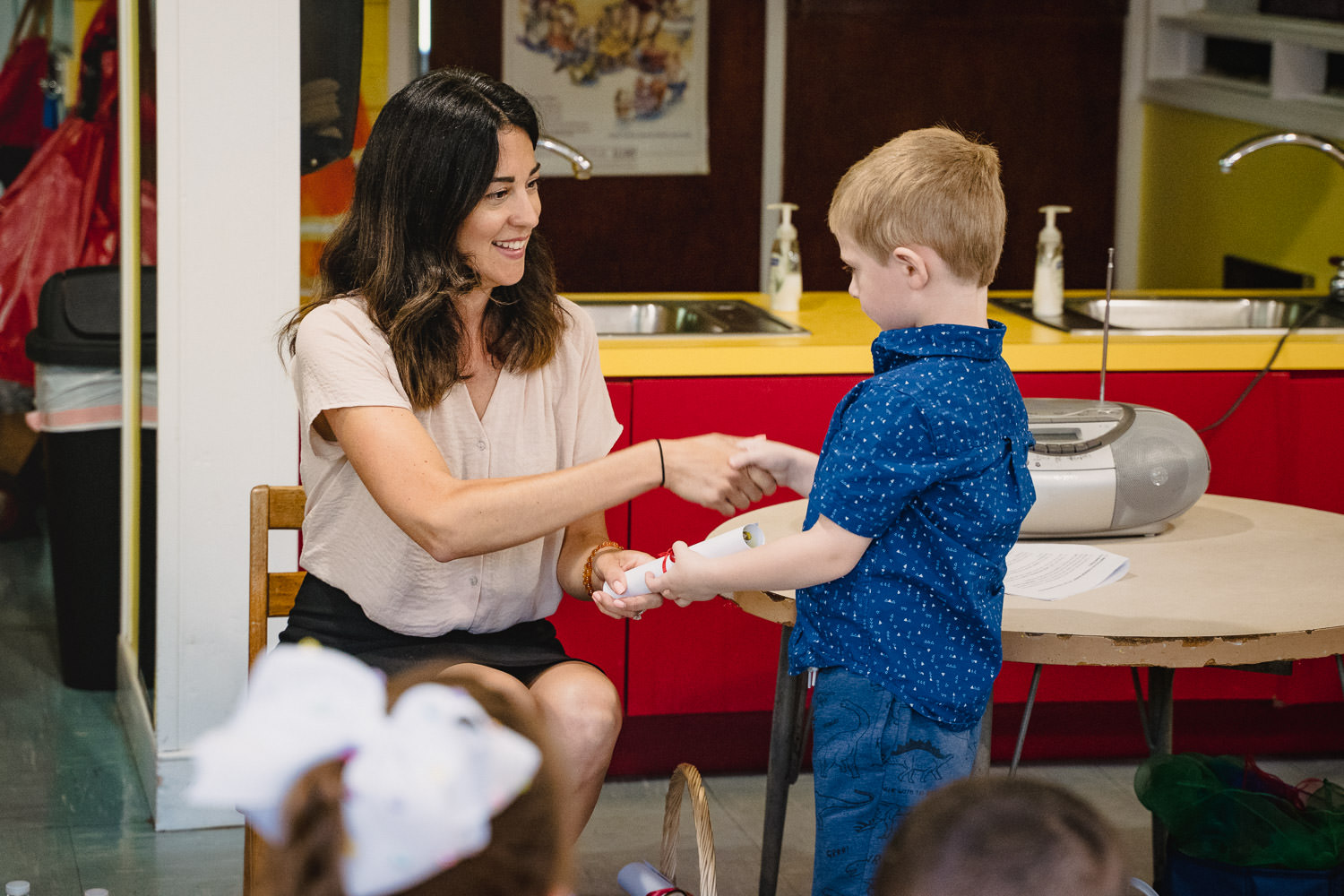 A little boy receives his pre-K diploma from his teacher.